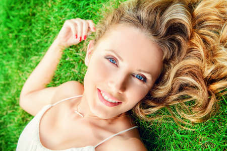 a serene life: Close-up portrait of a beautiful smiling woman lying on a grass outdoor. She is absolutely happy. Stock Photo