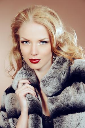 fur coat: Fashion shot of a beautiful young woman wearing fur coat. Studio shot.