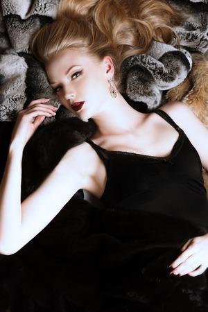 rubia: Mujer joven imponente con hermoso pelo rubio acostado en pieles. Lujo, rico estilo de vida. Joyería. Disparo de moda. Foto de archivo