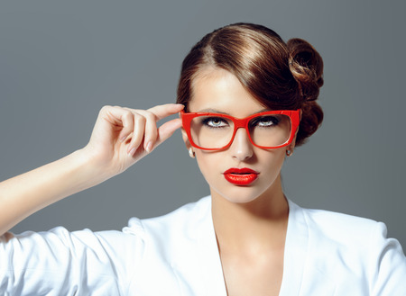 fascinating: Close-up portrait of a gorgeous young woman wearing glasses. Beauty, fashion. Make-up. Optics, eyewear. Stock Photo