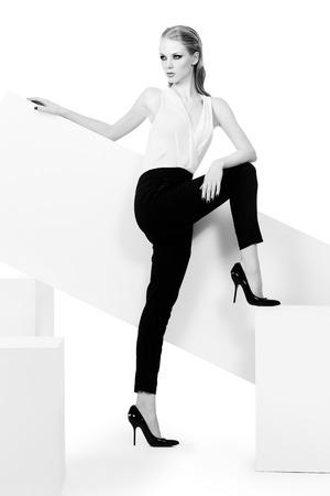 shoe model: Fashionable female model posing at studio. Beauty, fashion photo. Clothing. Body care. Isolated over white. Stock Photo