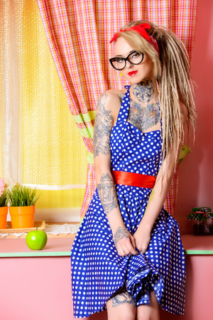 Modern pin-up girl wearing old-fashioned polka-dot dress and modern hairstyle dreadlocks. Fashion shot. Mixture of styles. Stock Photo