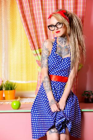tatouage sexy: Moderne fille de pin-up avec une robe à pois à l'ancienne et des dreadlocks de coiffure modernes. tir de mode. Mélange de styles. Banque d'images