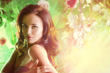 bronzed: Close-up portrait of a beautiful brunette woman among tropical plants. Beauty, fashion. Spa, healthcare. Tropical vacation. Stock Photo
