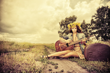 hippie: Romantic girl in a wreath of wild flowers travelling with her guitar. Summer. Hippie style.