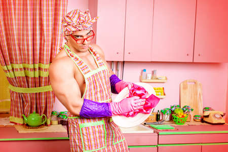 householder: Handsome muscular man in an apron cooking in the pink kitchen. Love concept. Valentines day. Stock Photo
