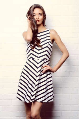 Beautiful lady in black-and-white dress posing near white brick wall. Beauty, fashion concept.