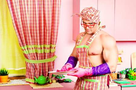 sexy funny: Handsome muscular man in an apron cooking in the pink kitchen. Love concept. Valentines day. Stock Photo
