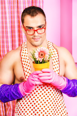 sexy birthday: Smiling muscular man in an apron stands with a flower  in the pink kitchen. Love concept. Valentines day. Womens day.
