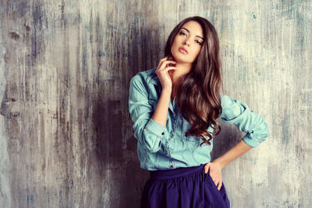 Красивая чувственная женщина в джинсовой одежды стоит на гранж стену. Мода.