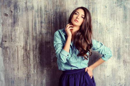 Gyönyörű érzéki nő farmerben ruhát áll a grunge falon. Divat.