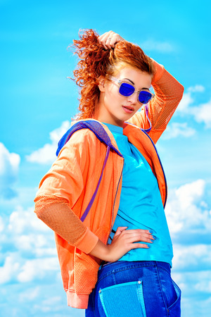 redhaired: Young stylish girl posing over blue sky. Youth fashion. Hip-hop style. Stock Photo