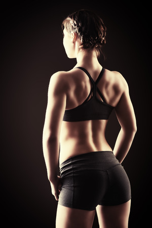 dorsi: Slender young woman with an athletic physique standing back. Fitness sports. Healthcare, bodycare. Black background.