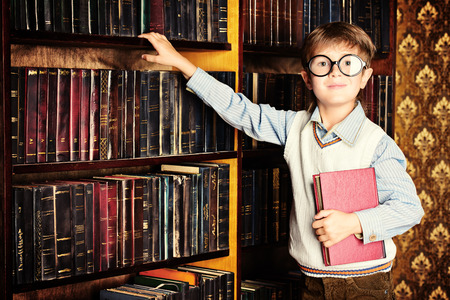 scientific literature: Smart boy stands in the library by the bookshelves with many old books. Educational concept. Science.