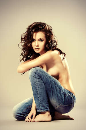 topless jeans: Sexual shirtless young woman alluring in jeans. Studio shot. Beauty, fashion.