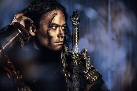 fantasy sword: Close-up portrait of the ancient male warrior in armor holding sword. Historical character. Fantasy. Stock Photo