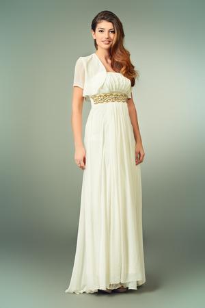 sexy bride: Full length portrait of a charming beautiful girl in elegant long white dress. Fashion shot. Stock Photo