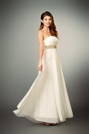 Full length portrait of a charming beautiful girl in elegant long white dress. Fashion shot. photo