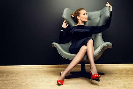 stile liberty: Ritratto di un modello alla moda sbalorditivo seduta su una sedia in stile Art Nouveau. Affari, elegante donna d'affari. Interni, mobili.