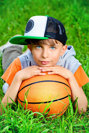 boy basketball: Cool boy lying on a grass with a basketball at a park. Summer day.