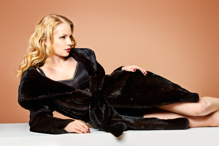 chaqueta: Mujer rubia hermosa que desgasta el abrigo de piel de vis�n. Moda, belleza. El estilo de vida de lujo. Estudio de disparo.