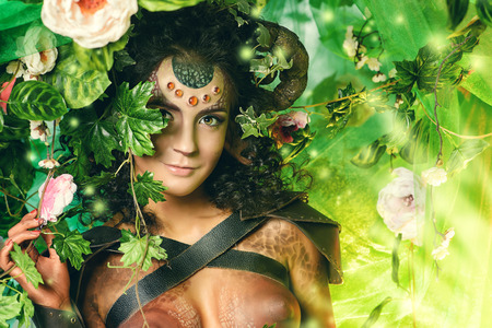 Art portrait of a fabulous female Faun in a fairy forest. Fantasy. Body painting.