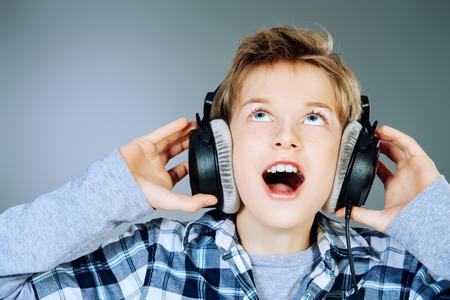 ni�o cantando: Muchacho adolescente alegre que escucha la m�sica en auriculares y cantando una canci�n. Estudio de disparo.