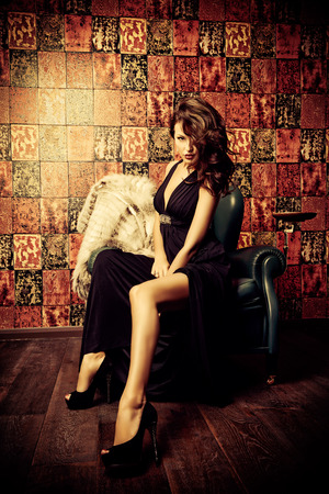 woman in fur coat: Beautiful charming woman in elegant evening dress and fur coat in a classic interior. Fashion, glamour.