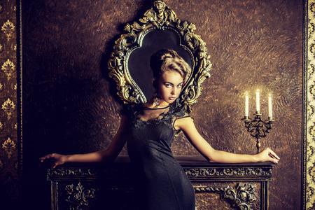 enchantress: Elegant young woman in black evening dress posing in vintage interior. Fashion shot.