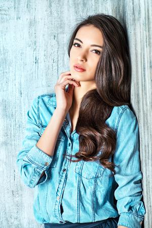 sexy young girl: Красивая чувственная женщина в джинсовой одежды стоит на гранж стену. Мода.