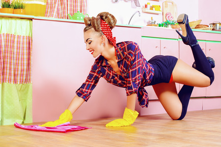 retro housewife: Pretty sexy pin-up girl cleans her glamorous pink kitchen. Retro style. Fashion. Stock Photo