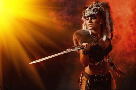 Beautiful bellicose Amazon with a sword in battle. Ancient times. Fantasy.