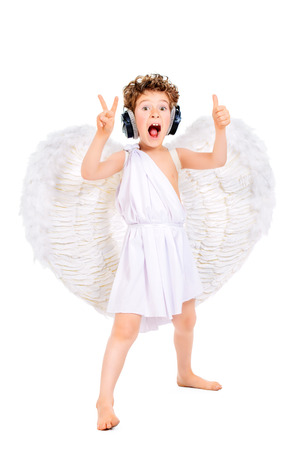 Cheerful little boy in a costume of angel listening to music in headphones and singing. Cupid. Valentines day. photo