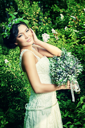 asian bride: Beautiful elegant asian bride in a summer park. Wedding dress and accessories. Stock Photo