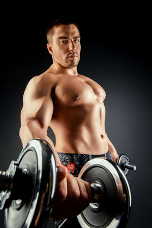 Handsome muscular man posing with dumbbells over black background. Bodybuilding. Professional sports. photo
