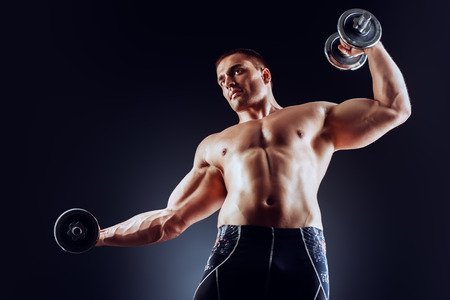 professional sports: Handsome muscular man posing with dumbbells over black background. Bodybuilding. Professional sports. Stock Photo