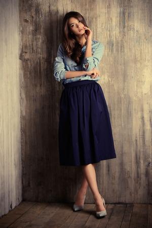 sensuales: Retrato de cuerpo entero de una hermosa mujer sensual en ropa de jeans se encuentra junto a la pared del grunge. La Moda. Foto de archivo