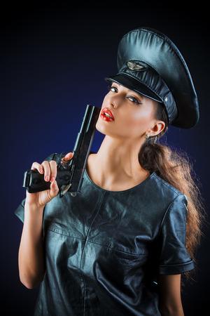 militaire sexy: Sexuelle jeune femme s�duisante en costume de cuir appropri� et une casquette de l'agent de police. Beaut�, mode.