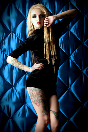 gothic woman: Sexual girl with black make-up and long dreadlocks wearing black dress. Gothic style. Fashion. Cosmetics, hairstyle. Tattoo. Stock Photo