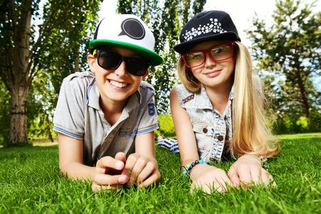 familias jovenes: Dos adolescentes alegres en el c�sped en el parque. Verano. Amistad. Foto de archivo