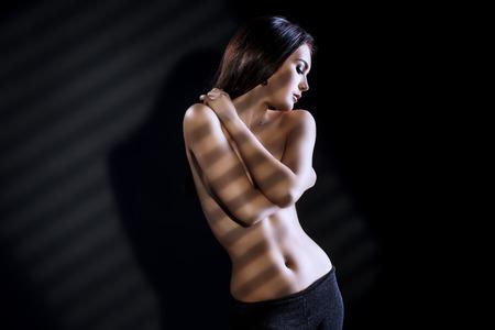 desnuda: Delgada hermosa mujer desnuda posando sobre fondo negro. Juego de luces y sombras. Foto de archivo