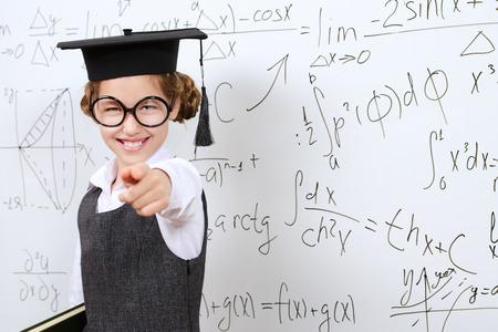 diligente: Colegiala elegante feliz en grandes gafas y sombrero académico realiza la tarea en la pizarra. Educación.