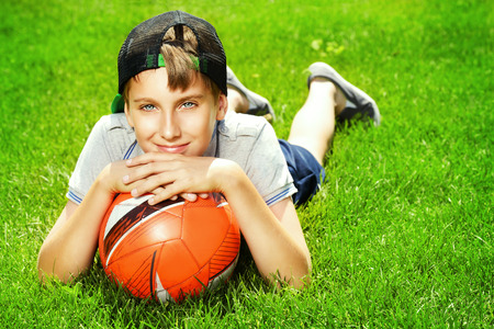 lying on grass: Cool boy lying on a grass with a football at a park. Summer day.
