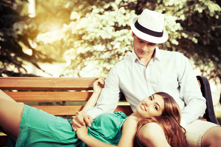 tenderly: Romantic young people tenderly  talking on a park bench. Love concept.