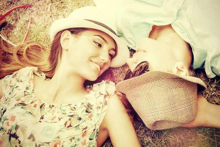 romance: Joven pareja feliz relajarse en el césped en un parque de verano. Concepto del amor. Vacaciones.