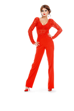 jumpsuit: Magnificent young woman in bright red suit posing at studio. Beauty, fashion. Full length portrait. Isolated over white.