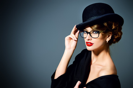 eyewear: Beautiful woman wearing glasses and bowler hat. Retro style. Beauty, fashion. Make-up. Optics, eyewear. Stock Photo