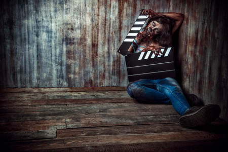 bloodthirsty: Filming a horror movie. Female zombie holding clapper board. Cinematography. Halloween.