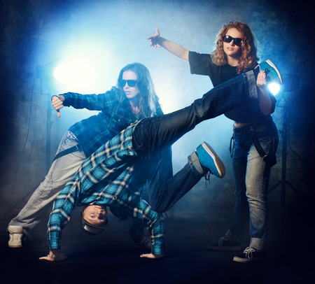 Group of modern dancers over grunge background. Urban, disco style. photo