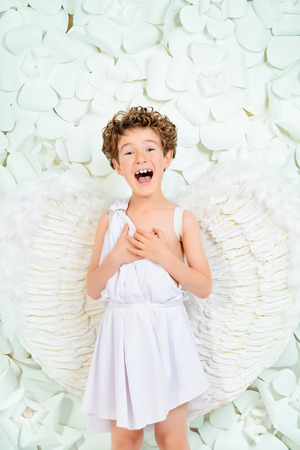 Portrait of a lovely emotional little boy in a costume of angel. Cupid. Valentines day. photo